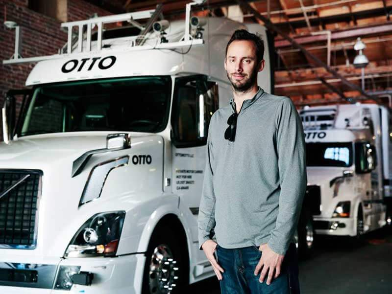 A man standing in front of two Otto's self-driving trucks