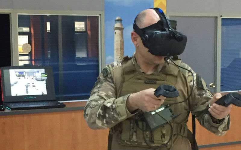 A soldier wearing a VR headset and holding VR controllers, with a laptop in the background