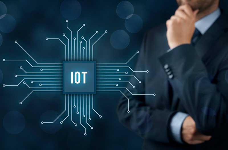 Man in suit thinking and looking at digital screen with IoT graphic