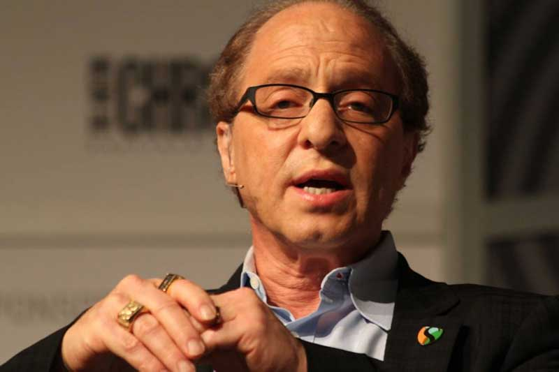 Ray Kurzweil sitting, wearing a microphone, and talking