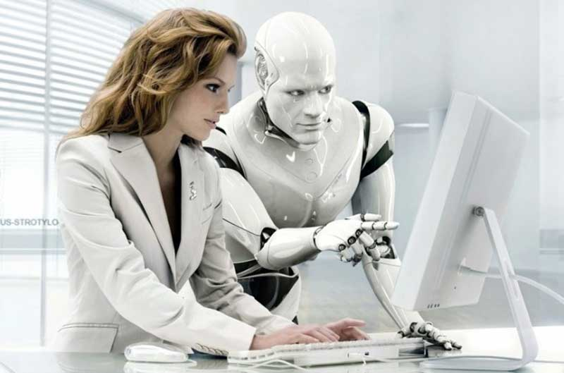 White robot and woman in white suit looking at computer screen