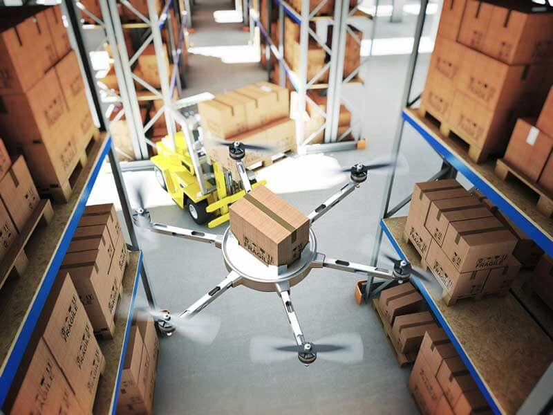 A drone carrying a package hovers inside a warehouse