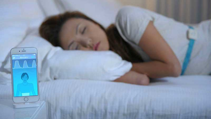Woman sleeping with a smartphone on the nightstand in front of her coaching her sleep