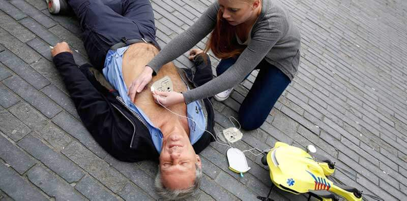 A man lying unconscious on the ground while a woman is attaching the defibrillator to his chest