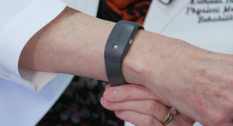 Black smart bracelet worn on a woman's wrist