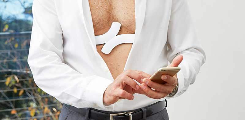 White QardioCore device on man's chest peaking through his unbuttoned white shirt