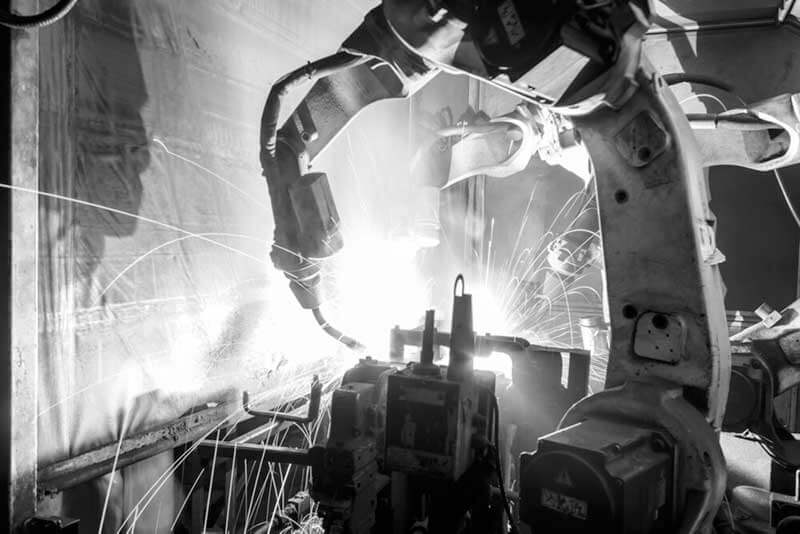 black-and-white photo of robotic arms welding