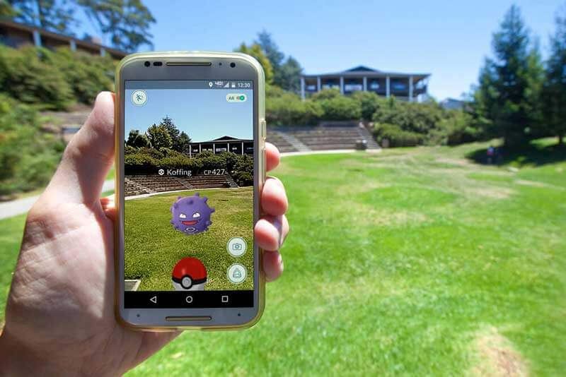 Hand holding a smartphone with Pokemon Go outdoors with greenery and a building in the background