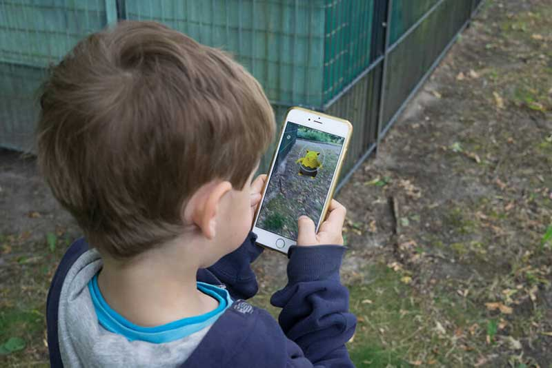 Child holding a smartphone and playing Pokemon Go outside