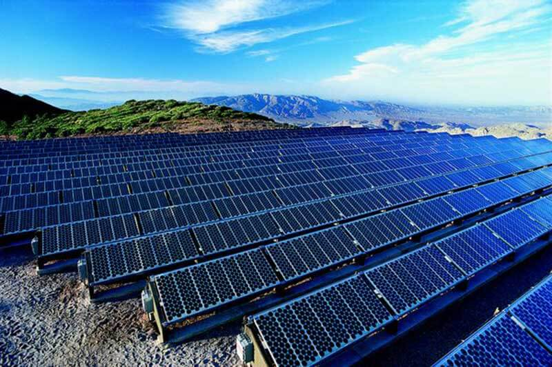 A solar farm with a green and mountainous landscape in the background
