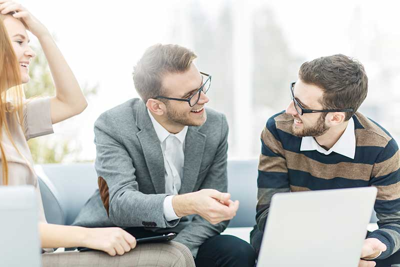 Two men and a woman having a meeting with laptop
