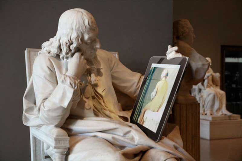 A sculpture of a man sitting down and it's holding a tablet-like device
