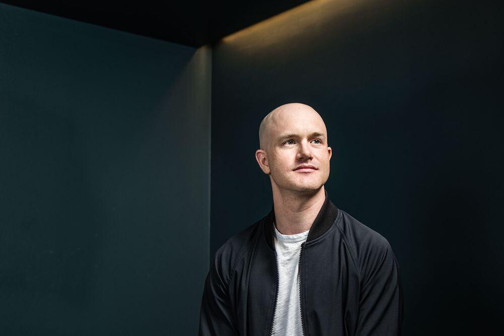 Een foto van Brian Armstrong, de CEO van Coinbase, met een wit T-shirt en een zwart jasje.